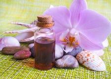 Αραβικό πετρέλαιο μασάζ Πέτρες και λουλούδι ορχιδεών με το φυσικό πετρέλαιο στο σαλόνι SPA Στοκ Φωτογραφίες