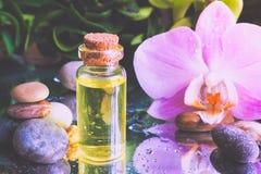 Αραβικό πετρέλαιο μασάζ Πέτρες και λουλούδι ορχιδεών με το φυσικό πετρέλαιο στο σαλόνι SPA Στοκ εικόνα με δικαίωμα ελεύθερης χρήσης