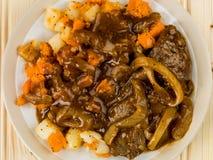 Αργά λαχανικά μπριζόλας και ρίζας με το ζωμό κρεμμυδιών Στοκ Εικόνα