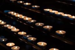 Αργά καίγοντας κεριά κεριών στην εκκλησία ως σύμβολο της μνήμης θανάτου Στοκ Εικόνες