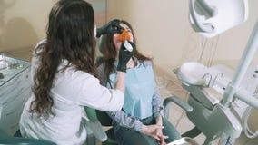 Αργά να πυροβολήσει τον οδοντίατρο στο γραφείο της που τίθεται μια σφραγίδα στο νέο κορίτσι στον ασθενή και την θερμαίνει με το α φιλμ μικρού μήκους