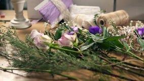 Αργή μετακίνηση καμερών που παρουσιάζει ξύλινο πίνακα με τα λουλούδια, ψαλίδι, ταινίες, διακοσμώντας το έγγραφο και άλλα εργαλεία απόθεμα βίντεο