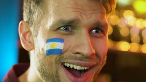 Αργεντινός οπαδός ποδοσφαίρου ευχαριστημένος από την αγαπημένη χρωματισμένη νίκη σημαία ομάδων στο μάγουλο απόθεμα βίντεο