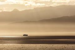 Αργυροειδές ηλιοβασίλεμα στο ναυάγιο με τις σειρές βουνών που σκιαγραφούνται στο υπόβαθρο Στοκ Φωτογραφία