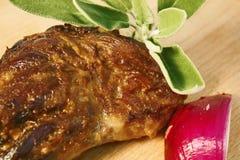Αργός ψητού ποδιών αρνιών που μαγειρεύεται επιδειγμένος στον ξύλινο τέμνοντα πίνακα με το κόκκινο κρεμμύδι και τα φρέσκα φύλλα με στοκ φωτογραφία με δικαίωμα ελεύθερης χρήσης