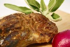 Αργός ψητού ποδιών αρνιών που μαγειρεύεται επιδειγμένος στον ξύλινο τέμνοντα πίνακα με το κόκκινο κρεμμύδι και τα φρέσκα φύλλα με στοκ φωτογραφία