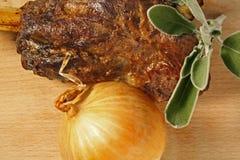 Αργός ψητού ποδιών αρνιών που μαγειρεύεται επιδειγμένος στον ξύλινο τέμνοντα πίνακα με το κρεμμύδι και τα φρέσκα φύλλα μεντών στοκ εικόνες με δικαίωμα ελεύθερης χρήσης