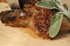 Αργός ψητού ποδιών αρνιών που μαγειρεύεται επιδειγμένος στον ξύλινο τέμνοντα πίνακα με τα φρέσκα φύλλα μεντών στοκ φωτογραφίες με δικαίωμα ελεύθερης χρήσης