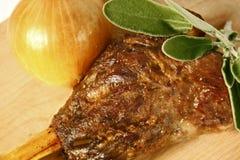 Αργός ψητού ποδιών αρνιών που μαγειρεύεται επιδειγμένος στον ξύλινο τέμνοντα πίνακα με το κρεμμύδι και τα φρέσκα φύλλα μεντών στοκ φωτογραφίες