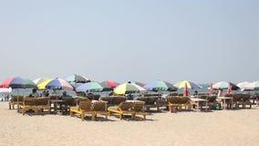 Αργόσχολοι παραλιών με τις χρωματισμένες ομπρέλες θαλάσσης σε μια αμμώδη παραλία στα πλαίσια της θάλασσας απόθεμα βίντεο