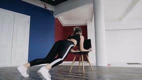 Αργό νέο αθλητικό κορίτσι που κάνει το τέντωμα ικανότητας, τα στοιχεία της γιόγκας και του tantra Περιπλέκει τους μυς workouts κα απόθεμα βίντεο