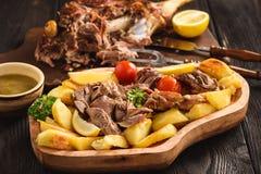 Αργό ψημένο πόδι αρνιών με τις πατάτες και τη σάλτσα Στοκ Φωτογραφία