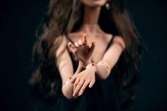 Αρθρωμένη κούκλα σε ένα μαύρο υπόβαθρο Όμορφη θηλυκή κινηματογράφηση σε πρώτο πλάνο χεριών στοκ εικόνα με δικαίωμα ελεύθερης χρήσης