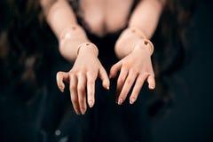 Αρθρωμένη κούκλα σε ένα μαύρο υπόβαθρο Όμορφη θηλυκή κινηματογράφηση σε πρώτο πλάνο χεριών στοκ εικόνα