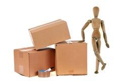 Αρθρωμένο ξύλινο μανεκέν εκτός από τα κουτιά από χαρτόνι και ένας ρόλος της κόλλας στο άσπρο υπόβαθρο στοκ φωτογραφία