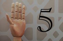 Αρθρωμένο ξύλινο χέρι με πέντε δάχτυλα που αυξάνονται στη νύξη στον αριθμό πέντε στοκ εικόνα