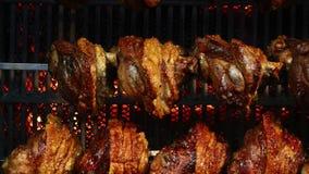 Αρθρώσεις χοιρινού κρέατος που μαγειρεύονται αργά στη σχάρα περιστροφής απόθεμα βίντεο