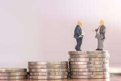 Αριθμοί επιχειρηματιών που στέκονται στο νόμισμα με θολωμένος backgroun Στοκ Εικόνα