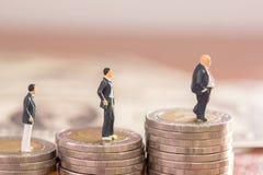 Αριθμοί επιχειρηματιών που στέκονται στο νόμισμα με θολωμένος backgroun Στοκ Φωτογραφία