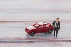 Αριθμοί επιχειρηματιών που στέκονται στο πάτωμα με το θολωμένο αυτοκίνητο Στοκ Εικόνες