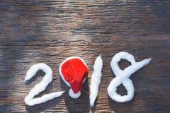 2018 αριθμοί καλής χρονιάς με το βαμβάκι και το κόκκινο καπέλο Άγιου Βασίλη Στοκ Φωτογραφίες