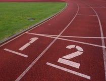 Αριθμός ένα και αριθμός δύο, κόκκινη λαστιχένια τρέχοντας πίστα αγώνων Στοκ εικόνα με δικαίωμα ελεύθερης χρήσης
