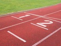 Αριθμός ένα και αριθμός δύο, κόκκινη λαστιχένια τρέχοντας πίστα αγώνων Στοκ φωτογραφίες με δικαίωμα ελεύθερης χρήσης