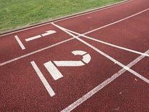 Αριθμός ένα και αριθμός δύο, κόκκινη λαστιχένια τρέχοντας πίστα αγώνων Στοκ εικόνες με δικαίωμα ελεύθερης χρήσης