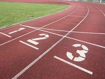 Αριθμός ένα και αριθμός δύο, κόκκινη λαστιχένια τρέχοντας πίστα αγώνων Στοκ φωτογραφία με δικαίωμα ελεύθερης χρήσης