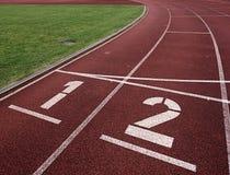 Αριθμός ένα και αριθμός δύο, κόκκινη λαστιχένια τρέχοντας πίστα αγώνων Στοκ Φωτογραφίες