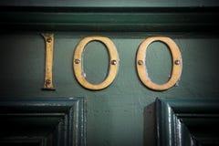 Αριθμός εκατό αριθμός πορτών ορείχαλκου στην ξεπερασμένη χρωματισμένη πόρτα Στοκ εικόνα με δικαίωμα ελεύθερης χρήσης
