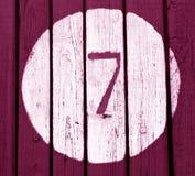 Αριθμός επτά στο ρόδινο τονισμένο ξύλινο τοίχο Στοκ Φωτογραφία