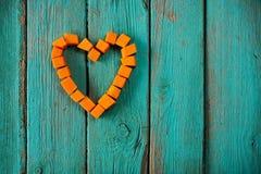 Αριθμός καρδιών φιαγμένος από κύβους κολοκύθας γλυκών πορτοκαλιών στην τυρκουάζ ΤΣΕ Στοκ εικόνα με δικαίωμα ελεύθερης χρήσης