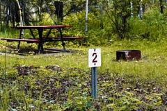 Αριθμός 2 μόνος δείκτης περιοχών στρατοπέδευσης εγγραφής με ένα κοίλωμα πινάκων και πυρκαγιάς πικ-νίκ στο υπόβαθρο Στοκ εικόνα με δικαίωμα ελεύθερης χρήσης