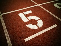 Αριθμός πέντε Μεγάλος άσπρος αριθμός διαδρομής στην κόκκινη λαστιχένια πίστα αγώνων Στοκ εικόνα με δικαίωμα ελεύθερης χρήσης