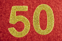 Αριθμός πενήντα κίτρινος πέρα από ένα κόκκινο υπόβαθρο εκμηδένισης Στοκ Φωτογραφία