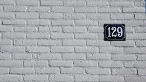 Αριθμός 129 στον άσπρο τοίχο Στοκ Εικόνες