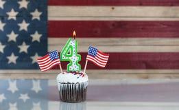 Αριθμός τέσσερα καψίματος κερί και μικρές ΑΜΕΡΙΚΑΝΙΚΕΣ σημαίες μέσα στα WI cupcake Στοκ Εικόνες