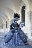 Αριθμός της Βενετίας καρναβάλι σε ένα ζωηρόχρωμο μαύρο και γκρίζο κοστούμι και μάσκα κάτω από το Arcade του Doges παλατιού Βενετί Στοκ Εικόνα