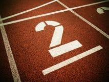 αριθμός δύο Μεγάλος άσπρος αριθμός διαδρομής στην κόκκινη λαστιχένια πίστα αγώνων Στοκ Εικόνες