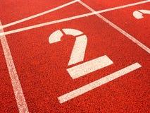 αριθμός δύο Μεγάλος άσπρος αριθμός διαδρομής στην κόκκινη λαστιχένια πίστα αγώνων Στοκ εικόνα με δικαίωμα ελεύθερης χρήσης