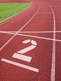 αριθμός δύο Μεγάλος άσπρος αριθμός διαδρομής στη λαστιχένια πίστα αγώνων τρεξίματος Στοκ Φωτογραφία