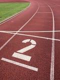 αριθμός δύο Μεγάλος άσπρος αριθμός διαδρομής στη λαστιχένια πίστα αγώνων τρεξίματος Στοκ Εικόνες