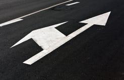 Αριστερό και ευθύ βέλος στην άσφαλτο Στοκ εικόνα με δικαίωμα ελεύθερης χρήσης