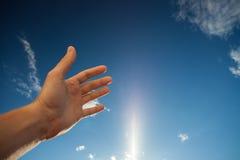 Αριστερό χέρι σχετικά με το μπλε ουρανό με τα σύννεφα στοκ εικόνες με δικαίωμα ελεύθερης χρήσης