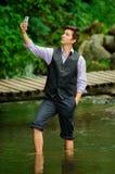 Αριστοκρατικός νεαρός άνδρας που παίρνει ένα selfie στη λίμνη στοκ εικόνες