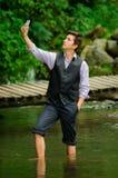 Αριστοκρατικός νεαρός άνδρας που παίρνει ένα selfie στη λίμνη στοκ φωτογραφίες