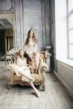 Αρκετά δίδυμο κορίτσι hairstyle αδελφών δύο ξανθό σγουρό στο εσωτερικό σπιτιών πολυτέλειας μαζί, πλούσια έννοια νέων στοκ φωτογραφίες