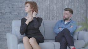 Αρκετά ανώτερη ώριμη γυναίκα που κοιτάζει μακριά και σχετικά με τη συνεδρίαση τρίχας της κοντά στον άνδρα στο μπλε πουκάμισο που  απόθεμα βίντεο