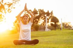 Αρκετά ασιατική γυναίκα που κάνει τις ασκήσεις γιόγκας στο πάρκο στοκ εικόνες με δικαίωμα ελεύθερης χρήσης
